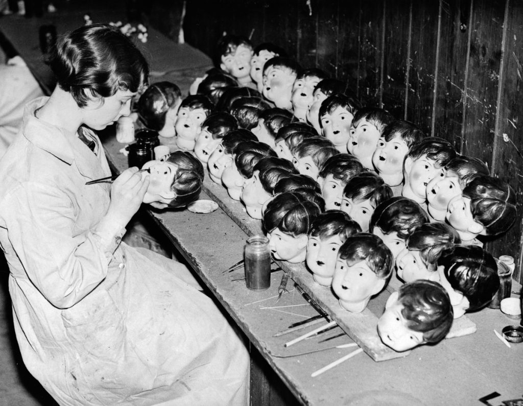 18th December 1935: A worker painting celluloid dolls heads at a factory in Leicester. (Photo by Harry Todd/Fox Photos/Getty Images)