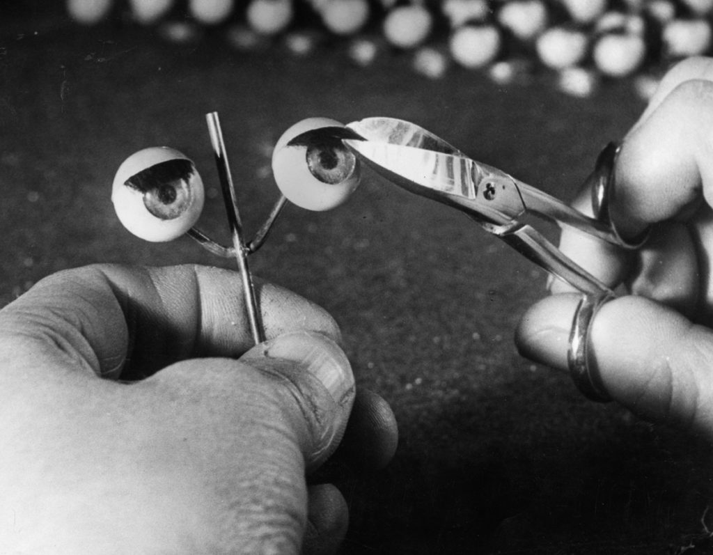 28th January 1949: A worker trims the eyelashes on a pair of doll's eyes at a factory in Totton, Southampton, which specialises in the manufacture of doll parts. (Photo by William Vanderson/Fox Photos/Getty Images)